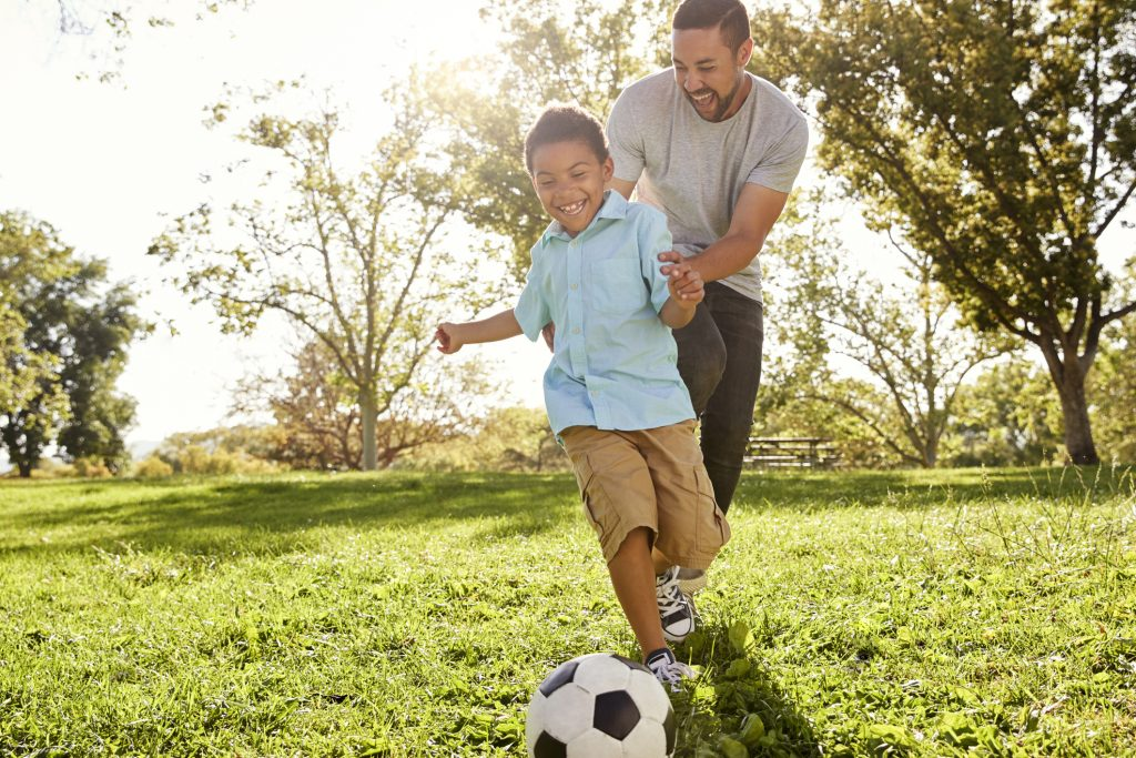 Father and son playing soccer in a park